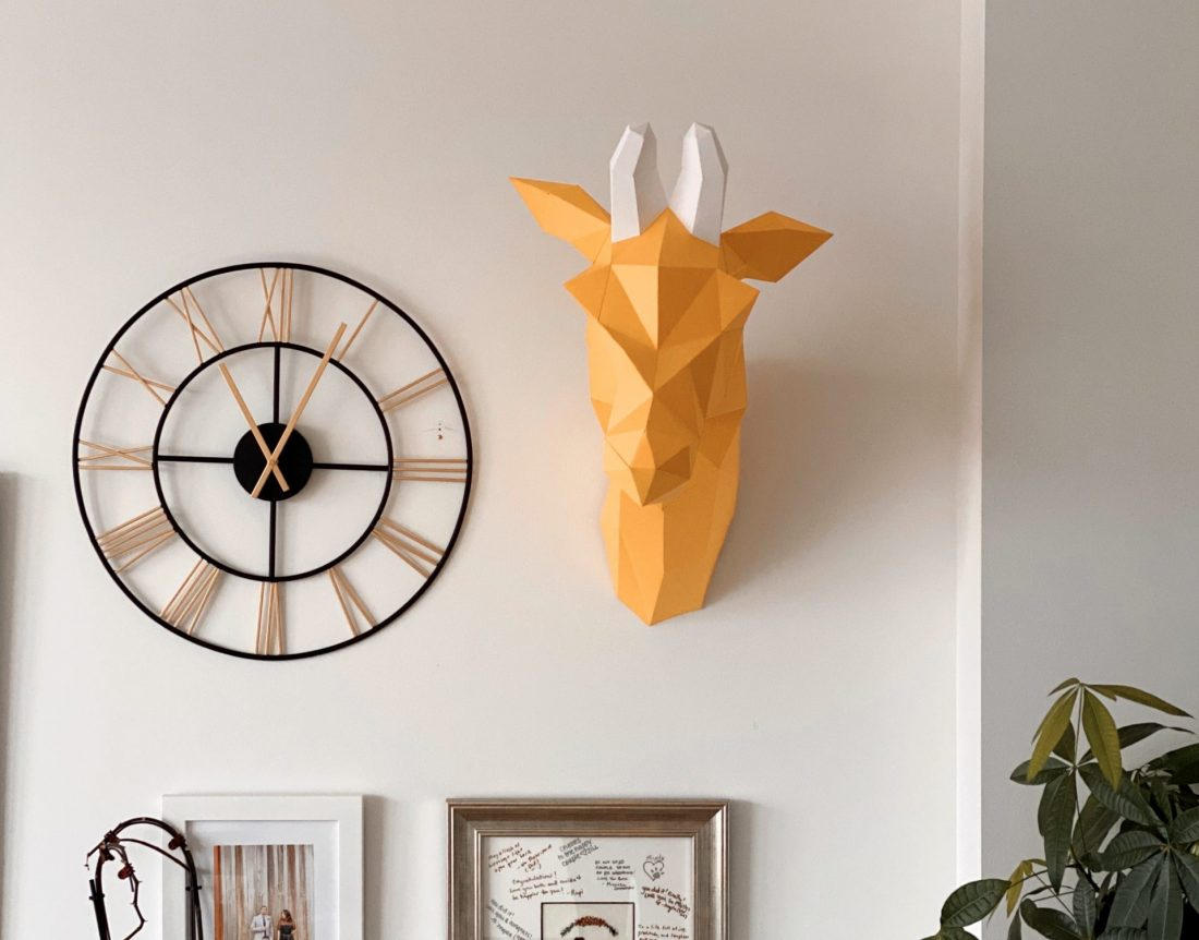 Finished Louise Giraffe paper craft on the wall next to clock and framed pictures
