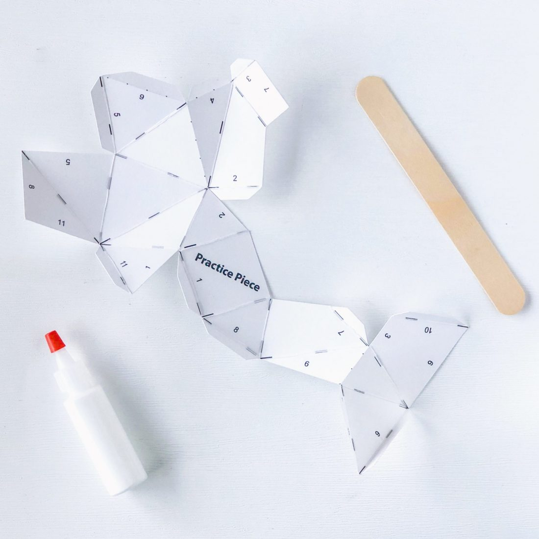 Practice paper whale materials: paper, glue bottle, and tongue depressor