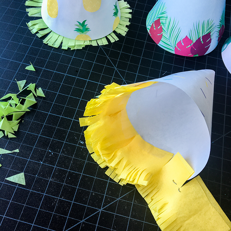 Taping Tissue Paper Fringe to DIY Paper Party Hats